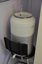 A homebrew kit fermenter sits on a stool