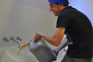 James pours wort into a fermenter that sits in a bath tub