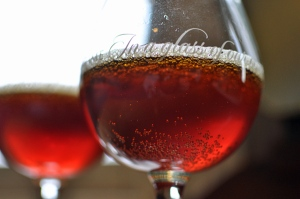 An upward view of two snifter glasses full of bright red Holgate's Beelzebub's Jewels, an oak aged Belgian style Quadrupel beer
