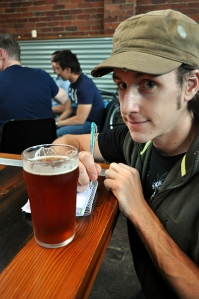 A younger me at Mountain Goat with pint of amber beer, pad and pen.