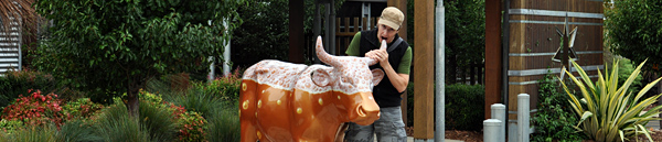 James eats the horn of a cow statue that has been painted like a beer