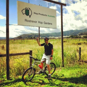 James on a bike under the sign for the Rostrevor Hop Gardens