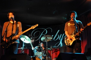 "Band photo of three piece ""Charm"" playing on the Ruby's Lounge stage"