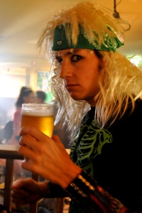 James dressed in 80s hair rock style with a pint of yellow beer
