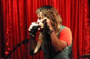 Lead singer, Pat, drinks his band's beer at Cherry Bar