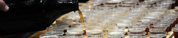 Banner image of growler pouring many samples of dark beer for tasting paddles