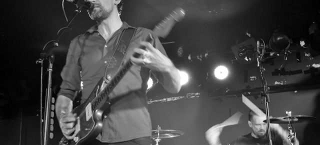 Black and white feature image of Something For Kate playing live