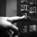 A hand presses buttons in an elevator