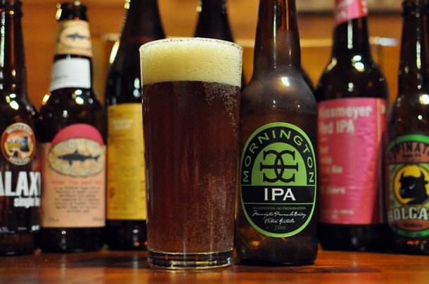 A bottle and full glass of Mornington IPA in front of other IPA beers