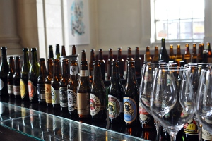 Many beer bottles lined up on a bar