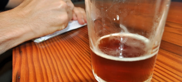 A glass of beer and in the background a hand is writing in a notepad