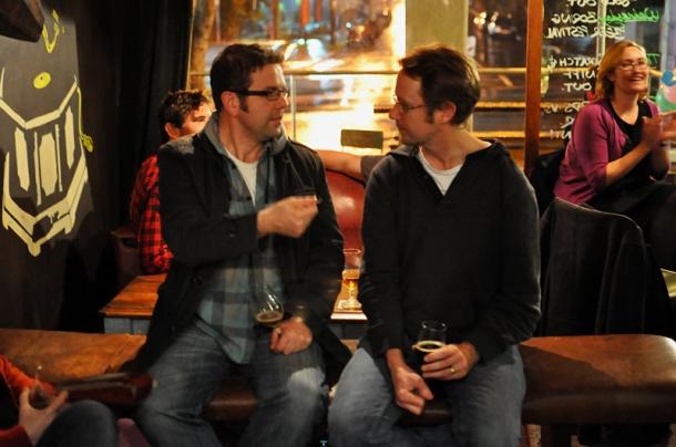 James Smith and Matt Kirkegaard chatting at a bar